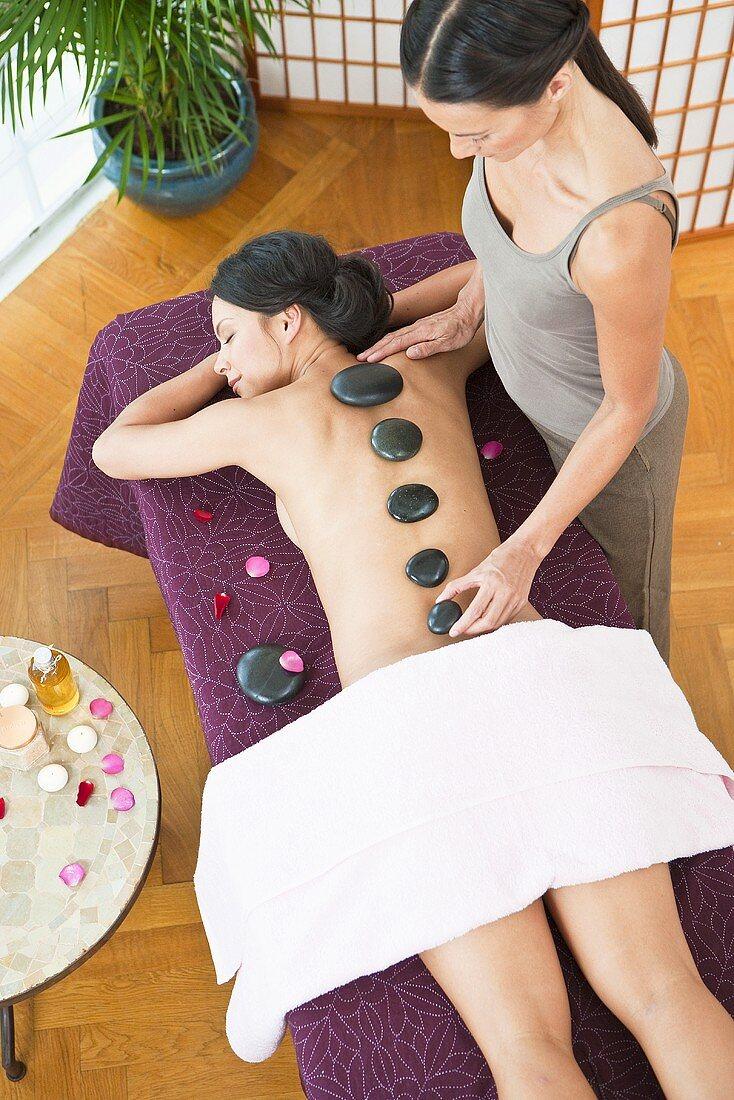 A woman having a La Stone massage in a spa