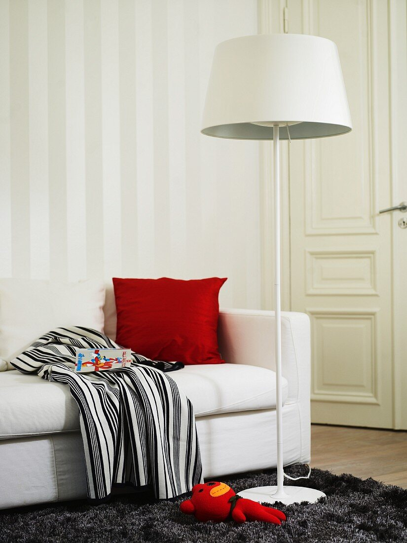 A sofa and a floor lamp in a bedroom
