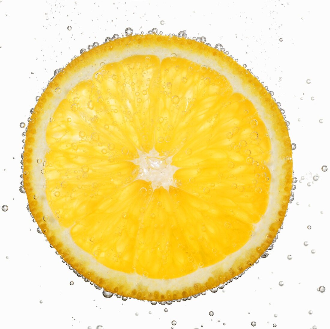 A slice of orange in water with air bubbles
