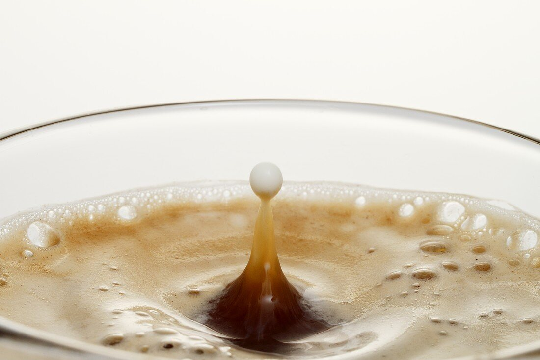 Cream dropping into coffee (close up)