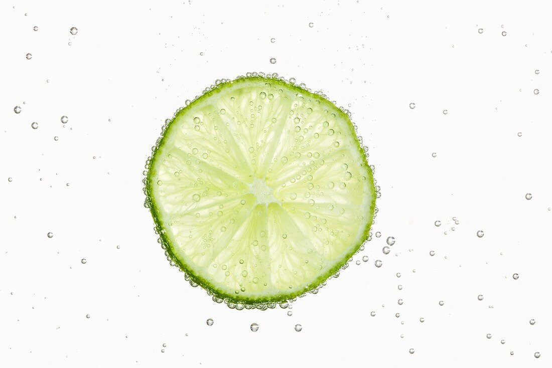 A slice of lime in water with air bubbles