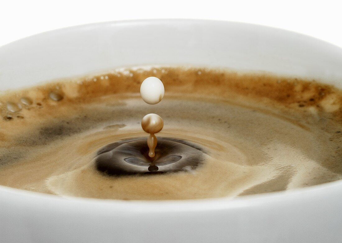 A drop of milk falling into a cup of coffee (close-up)