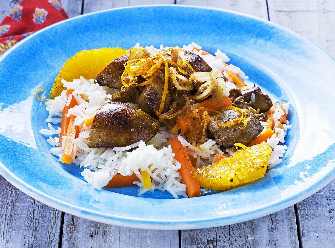 Lukewarm chicken liver salad with rice, carrots and oranges