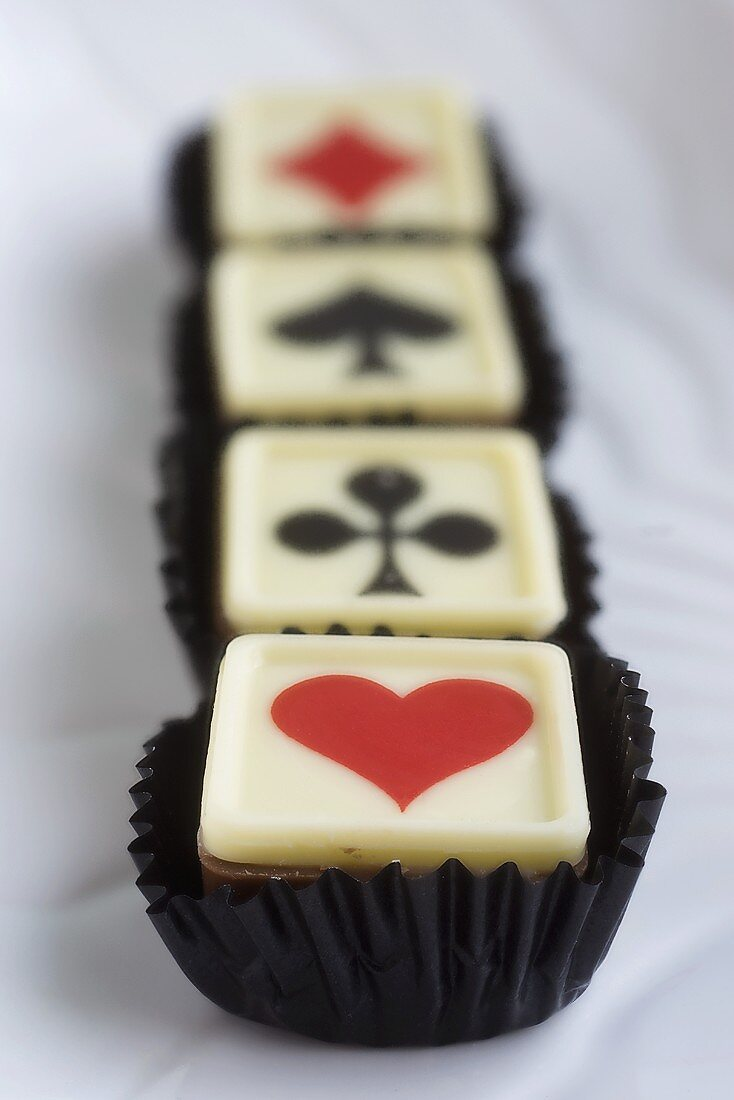 Four pralines with playing card symbols
