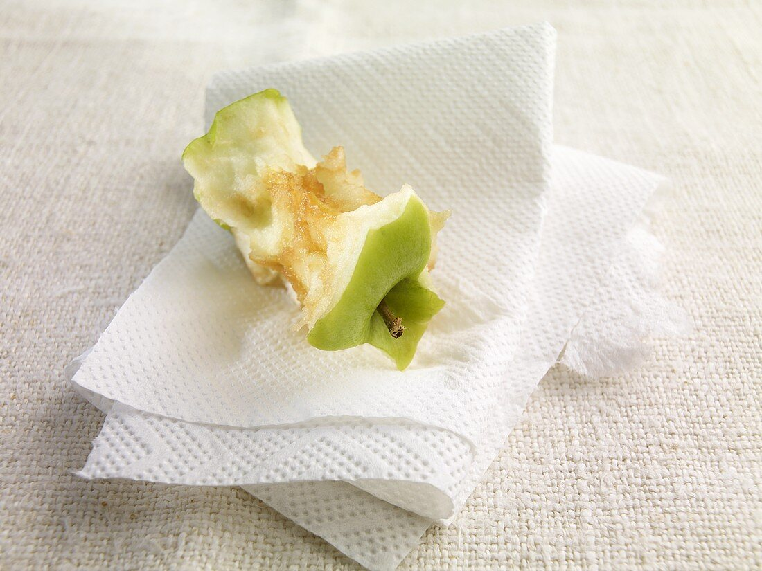 An apple core on kitchen paper