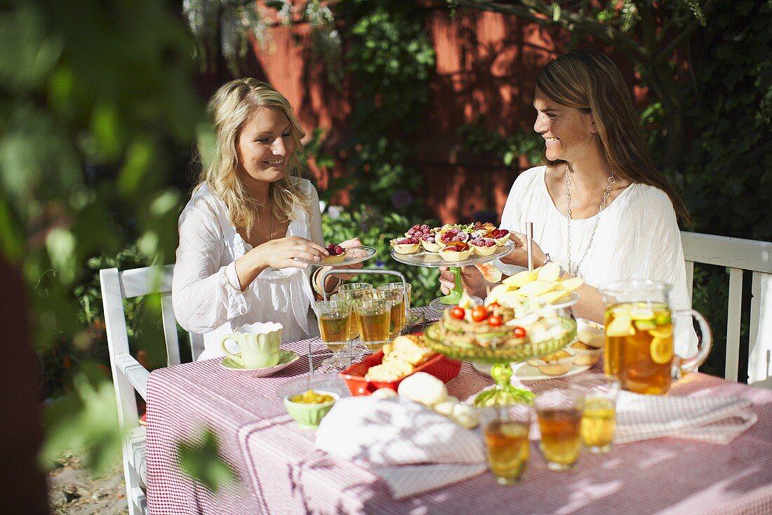 Two women drinking tea in a garden