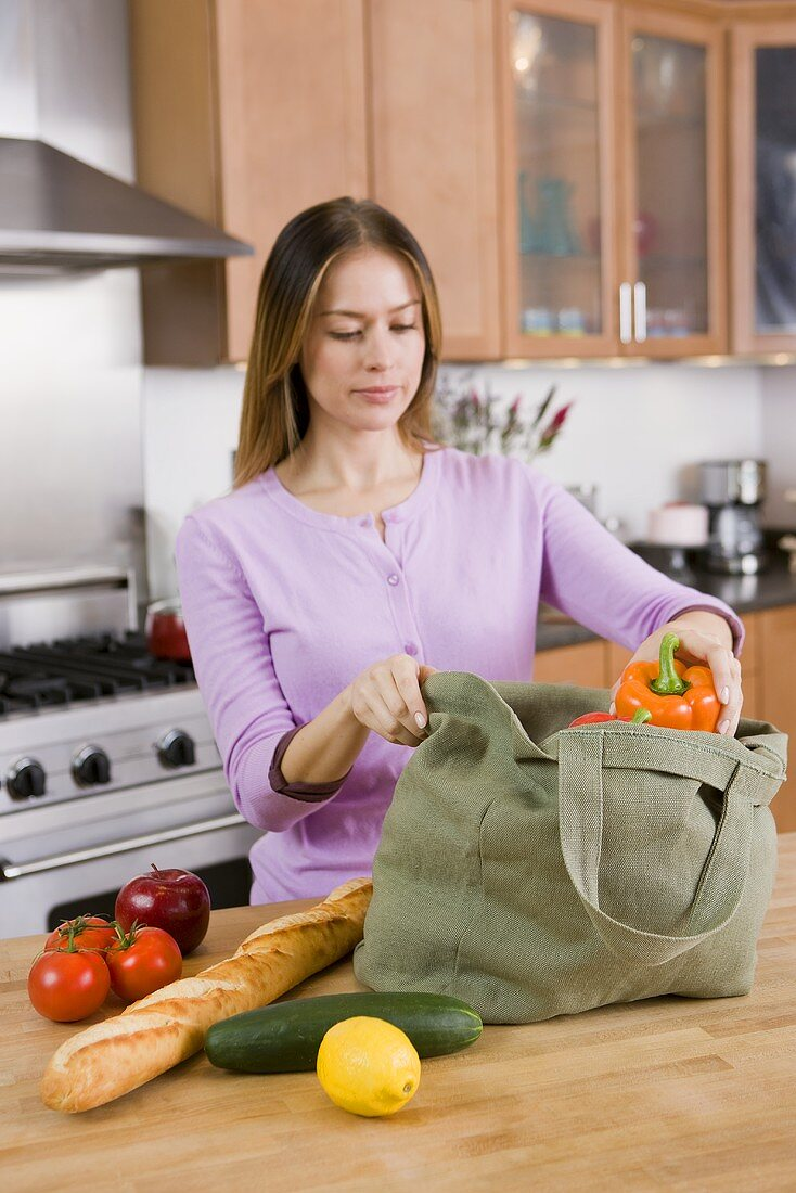 Woman Unloading Groceries from Cloth Bag on Kitchen Counter