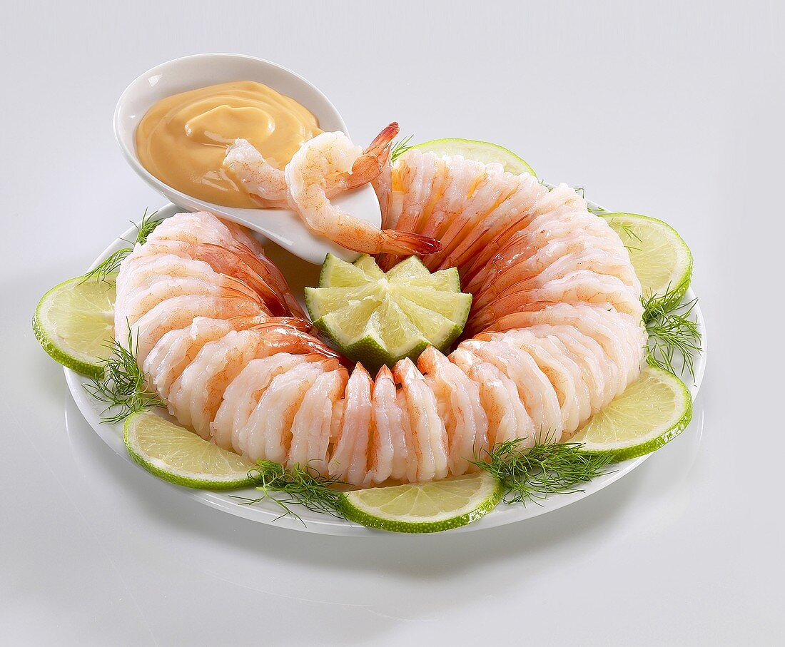 Ring of shrimp with cocktail sauce, limes and dill