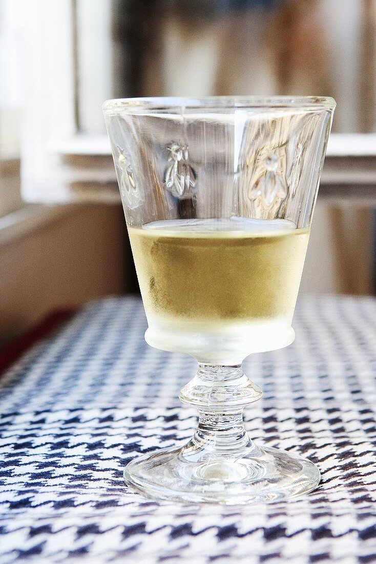 Cold Glass of White Wine on a Table in Paris, France