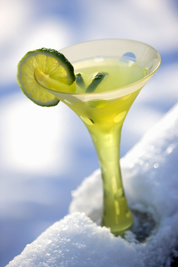 Lime Martini in Fun Stem Glass with Lime Garnish; On Snowy Railing