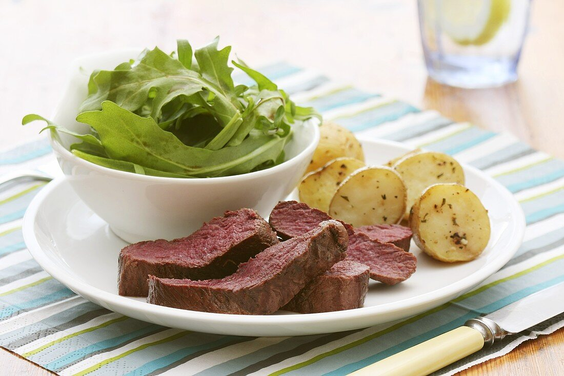 Fried ostrich fillet with a rocket salad and rosemary potatoes