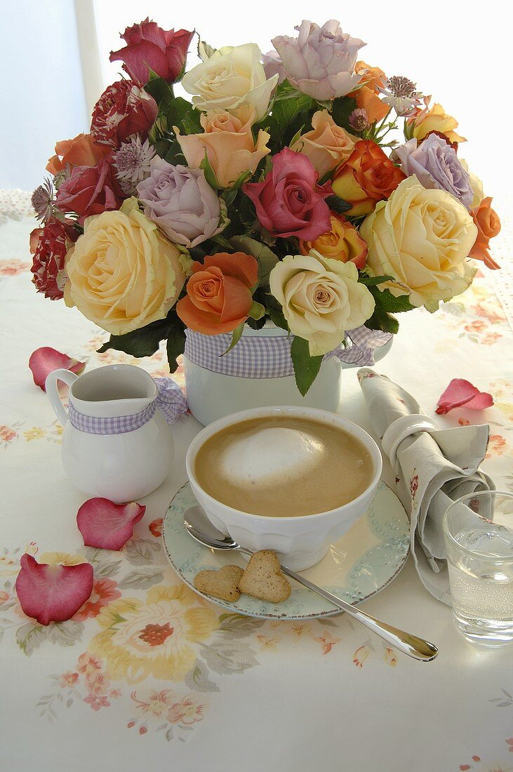 Cup of coffee, cream jug and vase of flowers