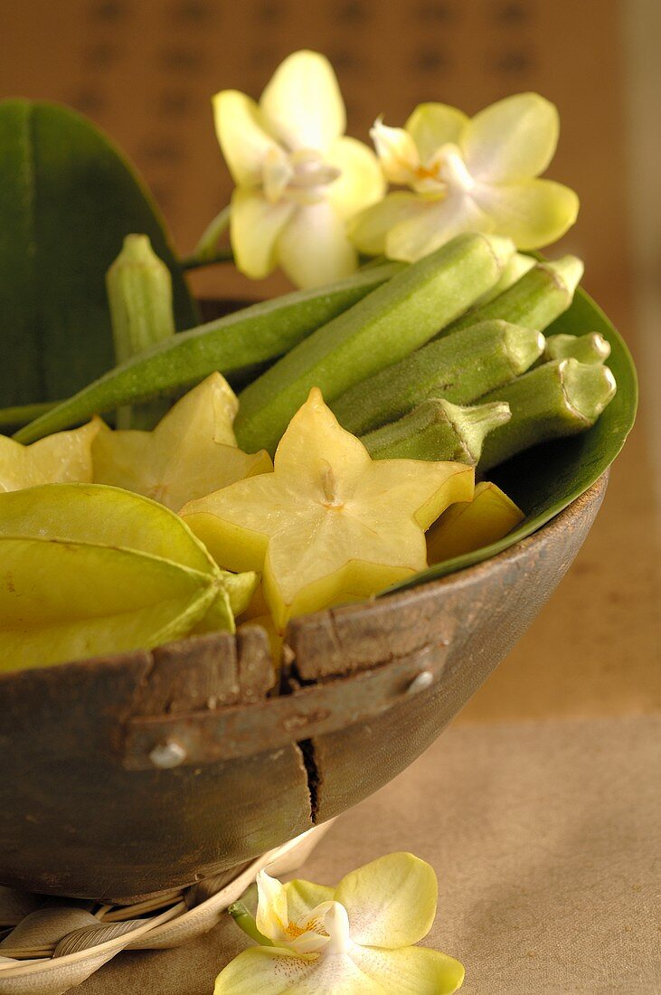 Carambolas, okra pods and orchids in wooden bowl