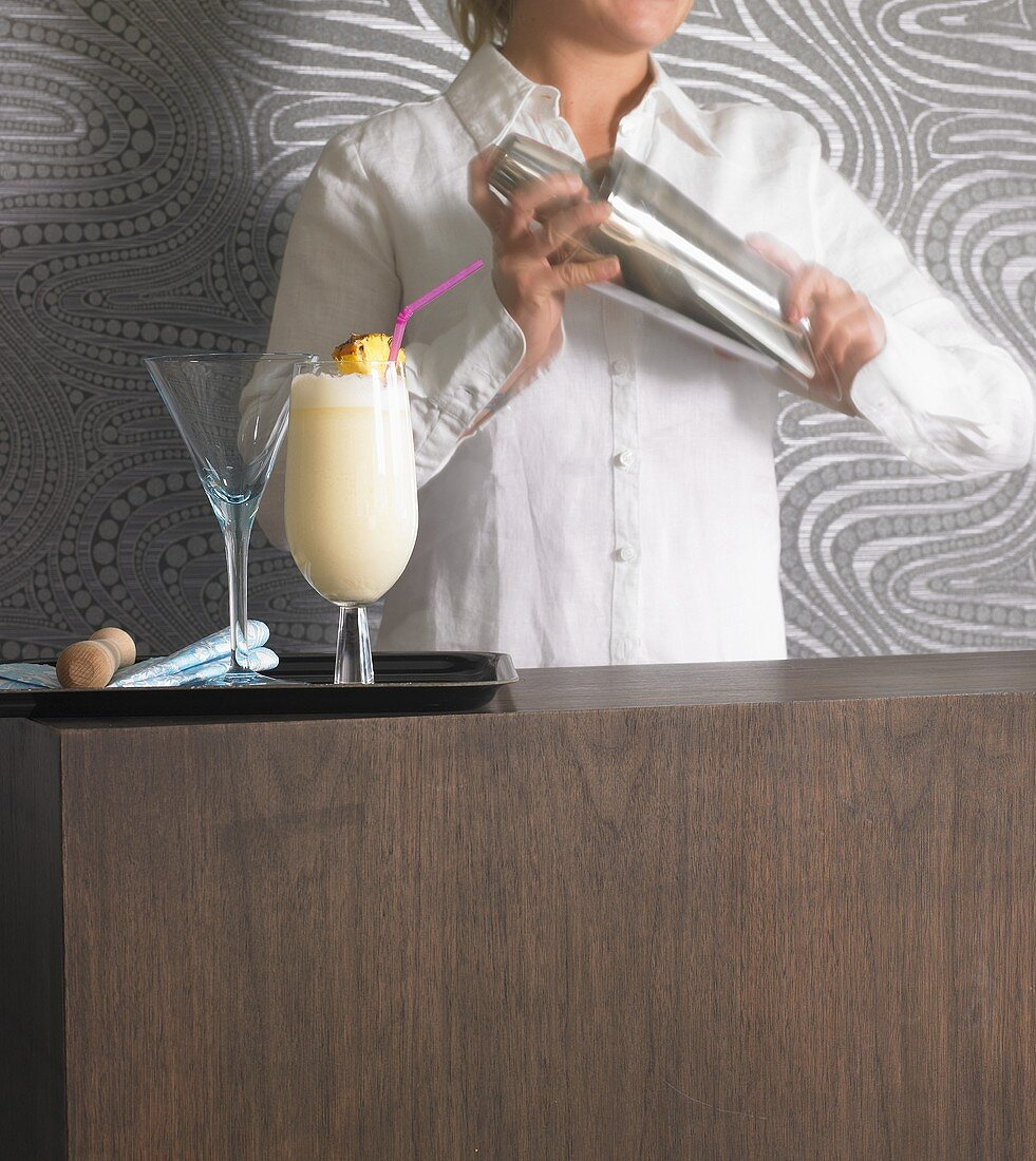 Woman mixing drink in cocktail shaker, pina colada on tray