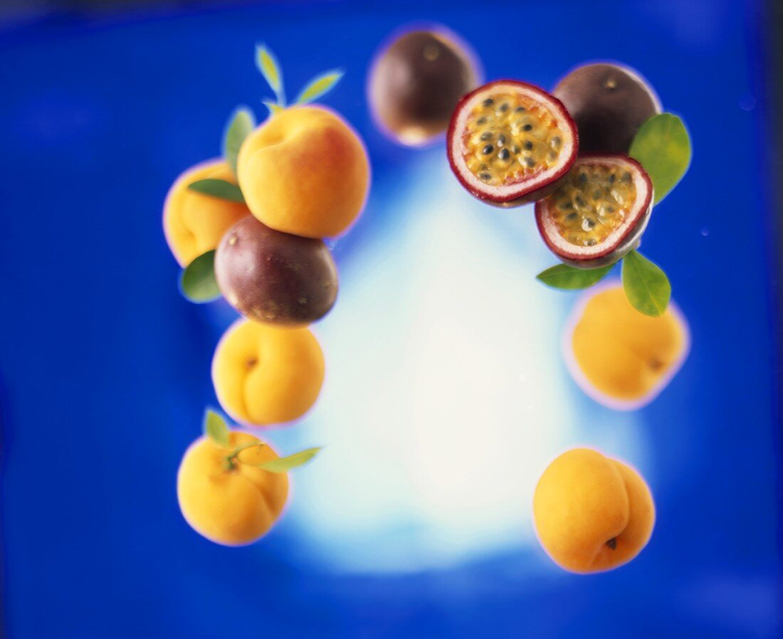 Several apricots, whole and half passion fruits