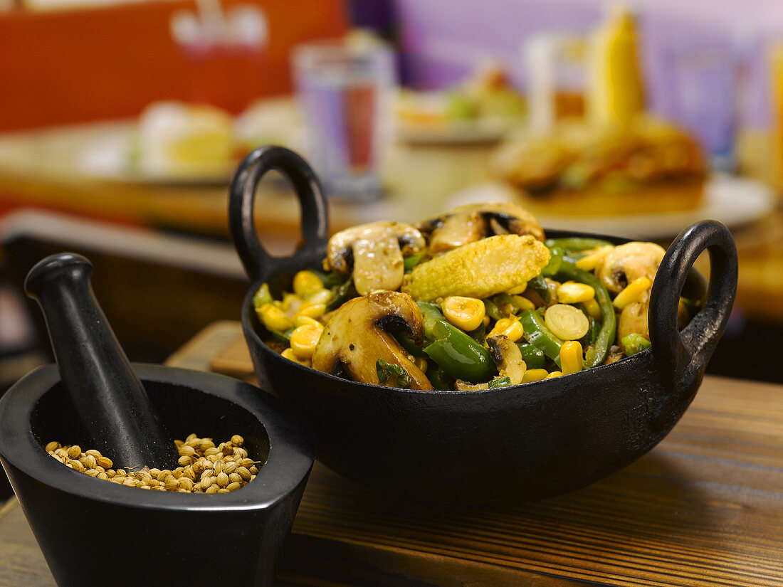 Stir-fried mushrooms, sweetcorn and beans in a small pan