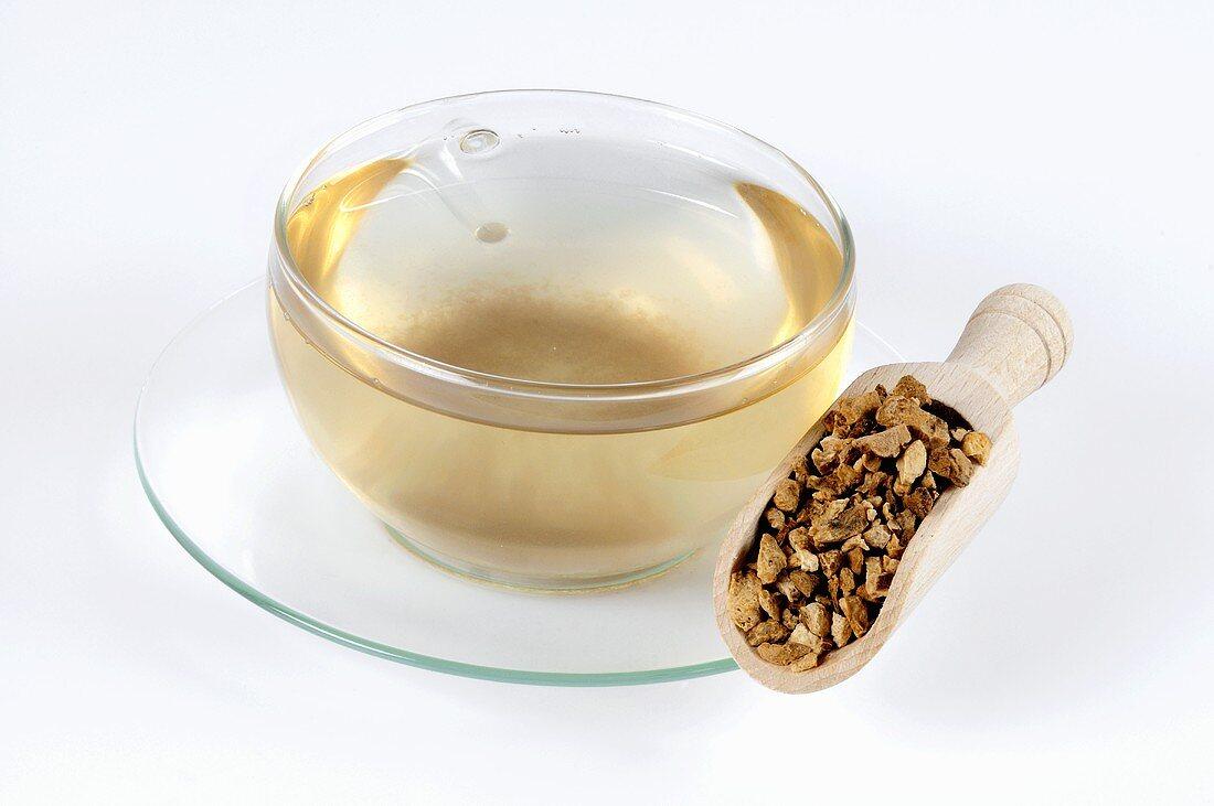 Tasse Tee mit getrockneter Atractylodes-Wurzel auf Schaufel