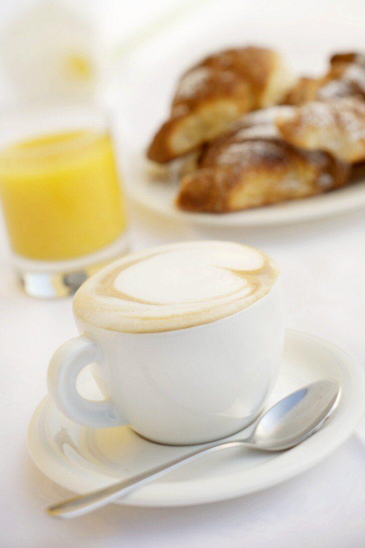 A cup of cappuccino, orange juice and brioches
