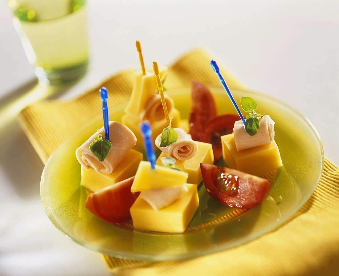 Cheese and ham on cocktail sticks with tomatoes