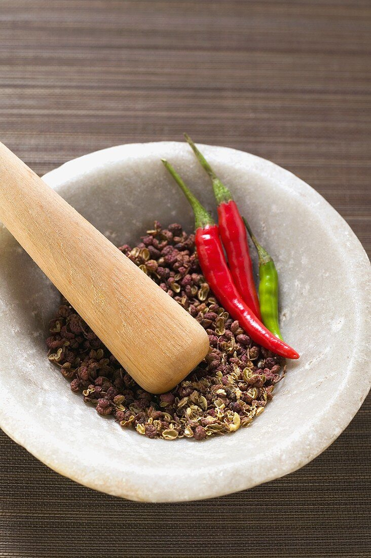 Szechuan pepper and chili peppers in mortar