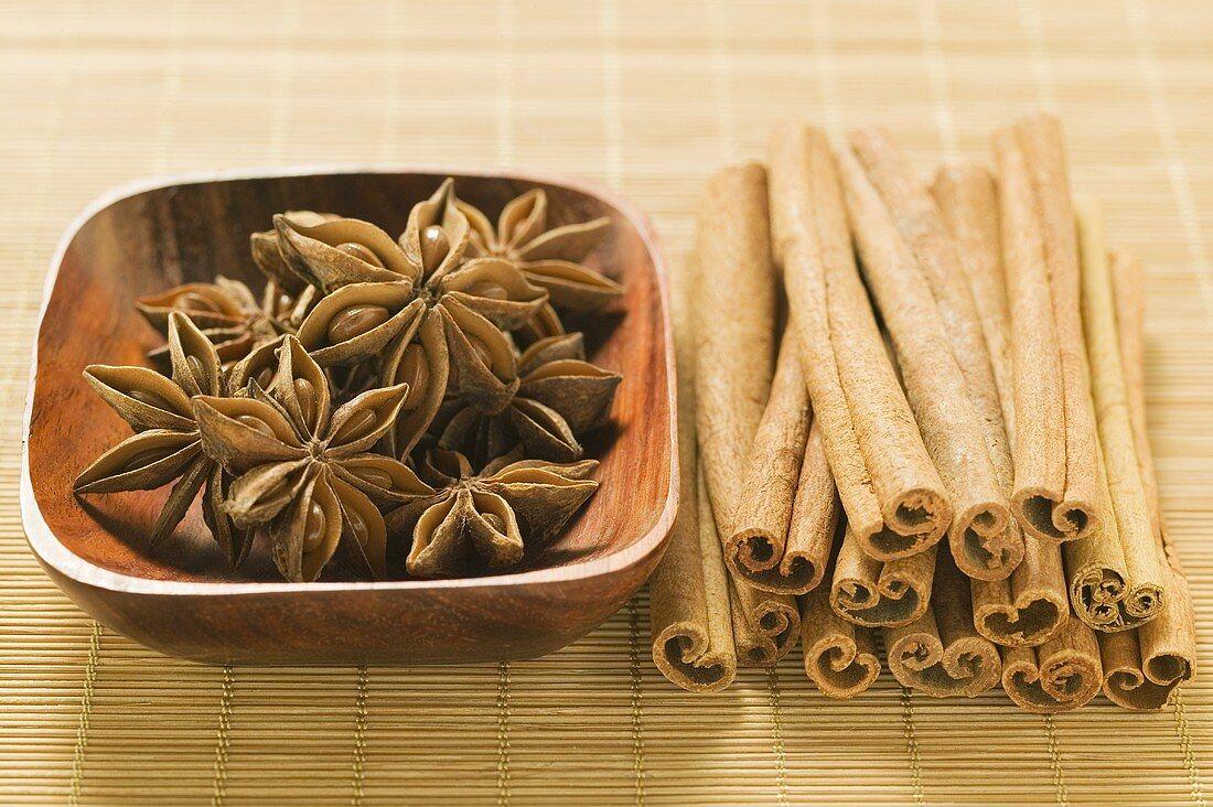 Star anise in wooden bowl, cinnamon sticks beside it