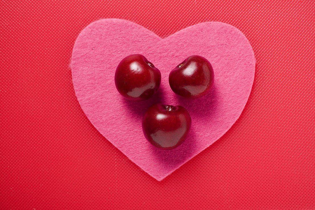 Three cherries on a pink felt heart