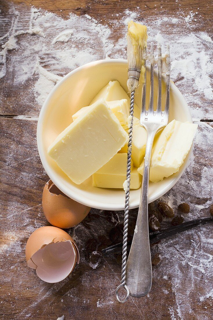 Butter in basin, eggshells, pastry brush and fork