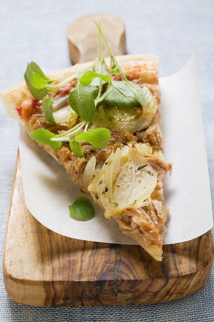 Slice of tuna and onion pizza with fresh oregano