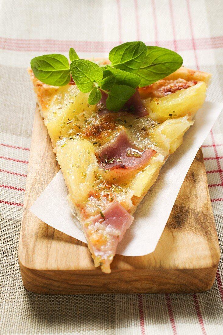 Slice of Hawaiian pizza with fresh oregano on chopping board