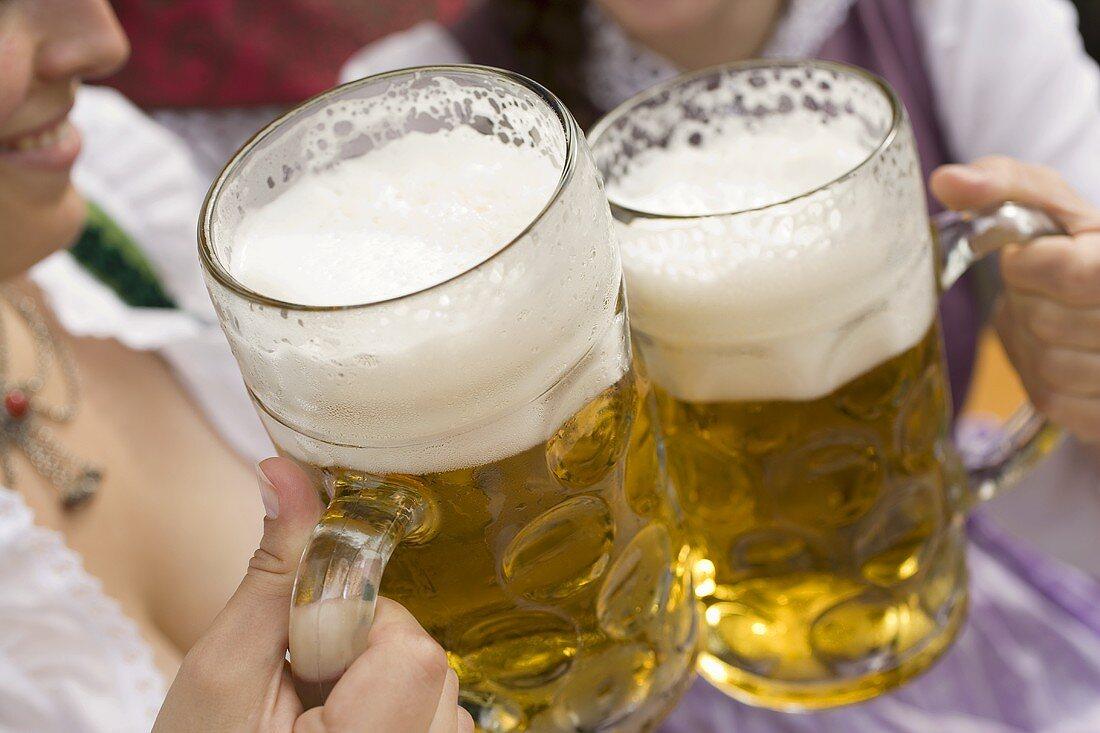 Hands clinking litres of beer together (Oktoberfest, Munich)