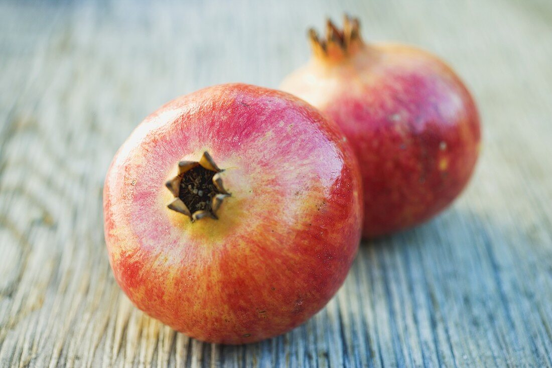 Two pomegranates on wooden background