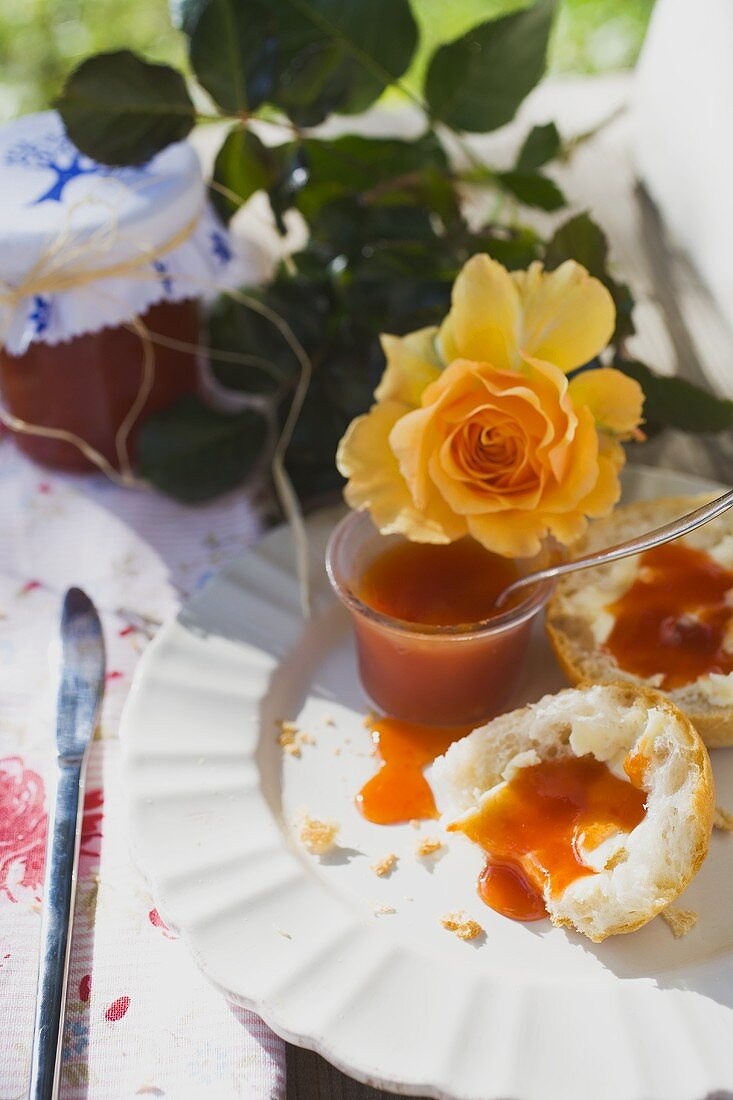 Rose hip jam on bread roll, yellow rose