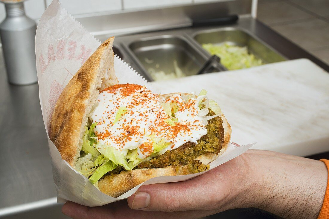 Pita bread filled with falafel, lettuce and yoghurt
