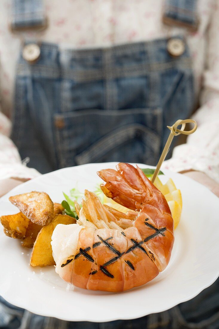 Person holding grilled king prawn on plate