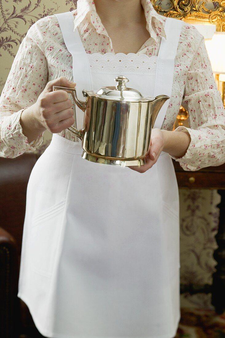 Chambermaid holding silver pot