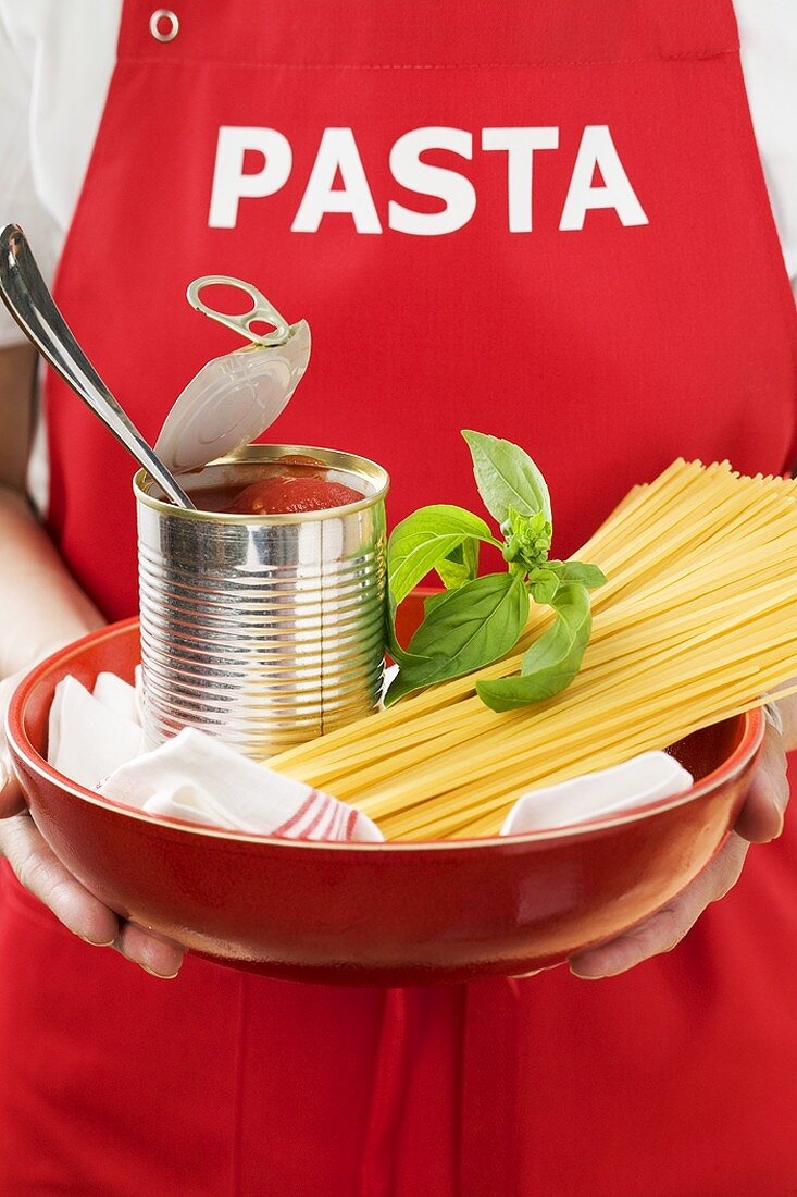 Woman holding spaghetti, tin of tomatoes and basil in dish