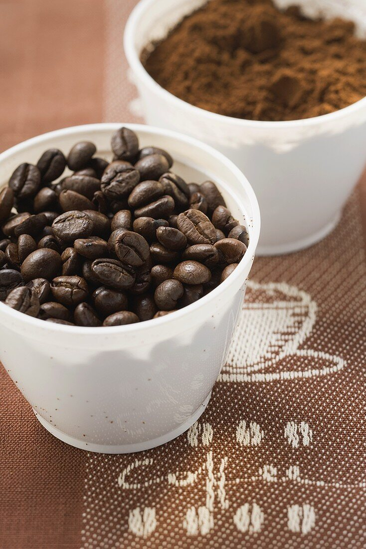Coffee beans and coffee powder in two beakers