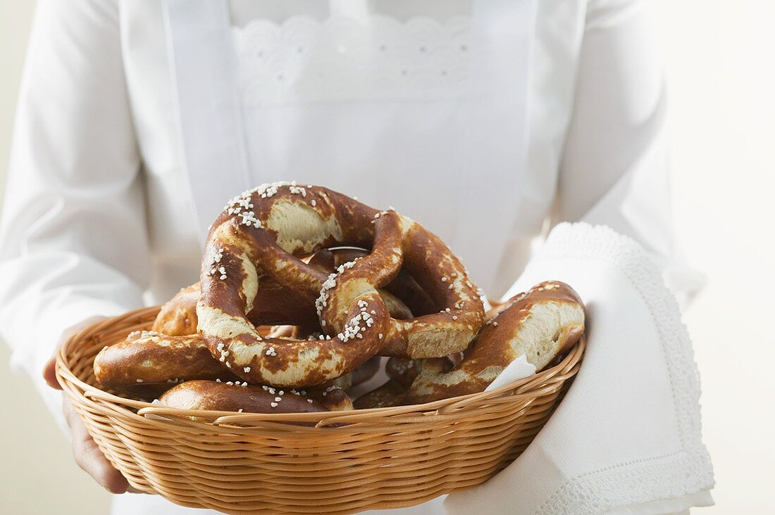 Chambermaid serving soft pretzels in bread basket