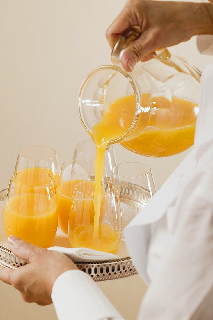 Chambermaid pouring orange juice into glass