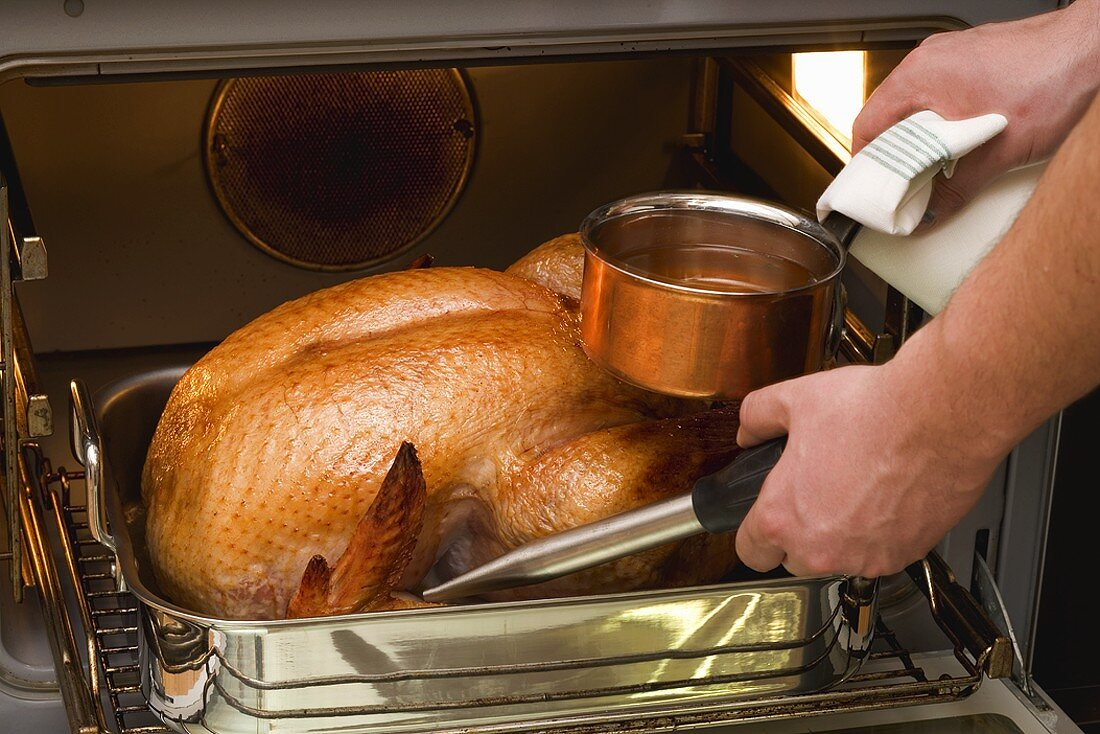 Basting turkey with roasting juices, in the oven