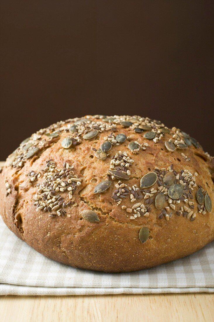 Wholemeal bread with pumpkin seeds on tea towel