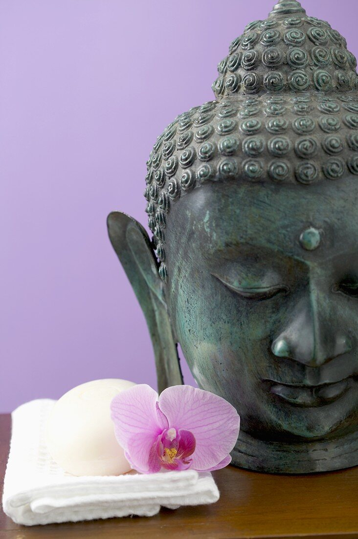 Orchid and soap on white towel beside statue of Buddha