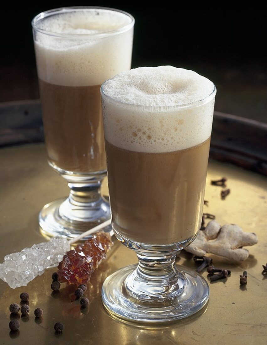 Beer grog in two glasses, spices, sugar swizzle sticks