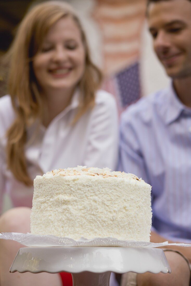 Coconut cake for the 4th of July, couple in background (USA)