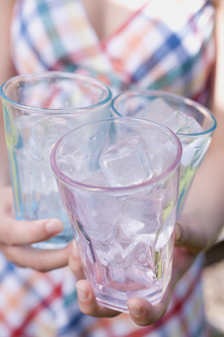 Woman holding three glasses filled with ice cubes