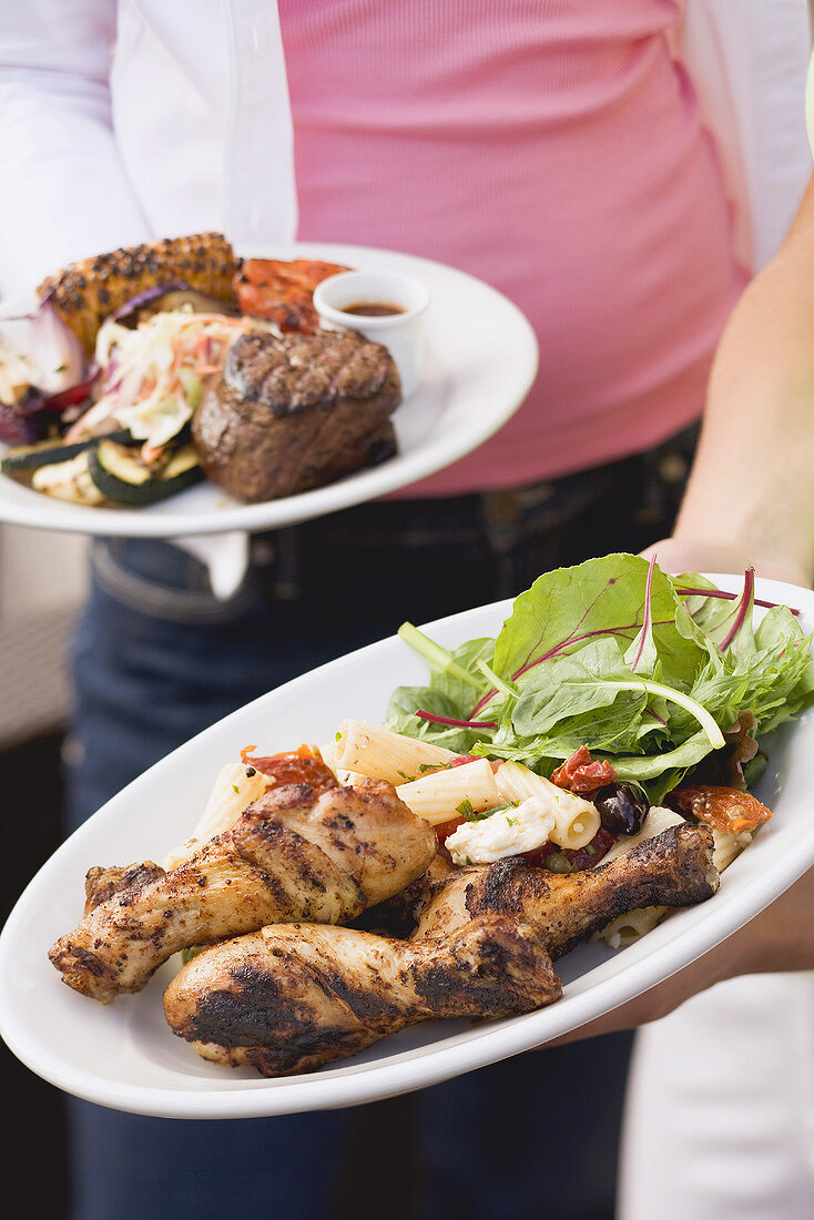 Two people holding plates of grilled food (different)