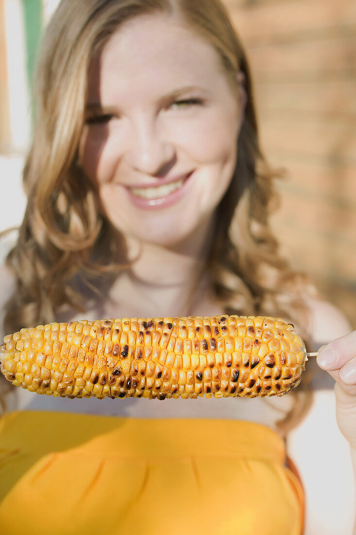 Woman holding grilled corn on the cob