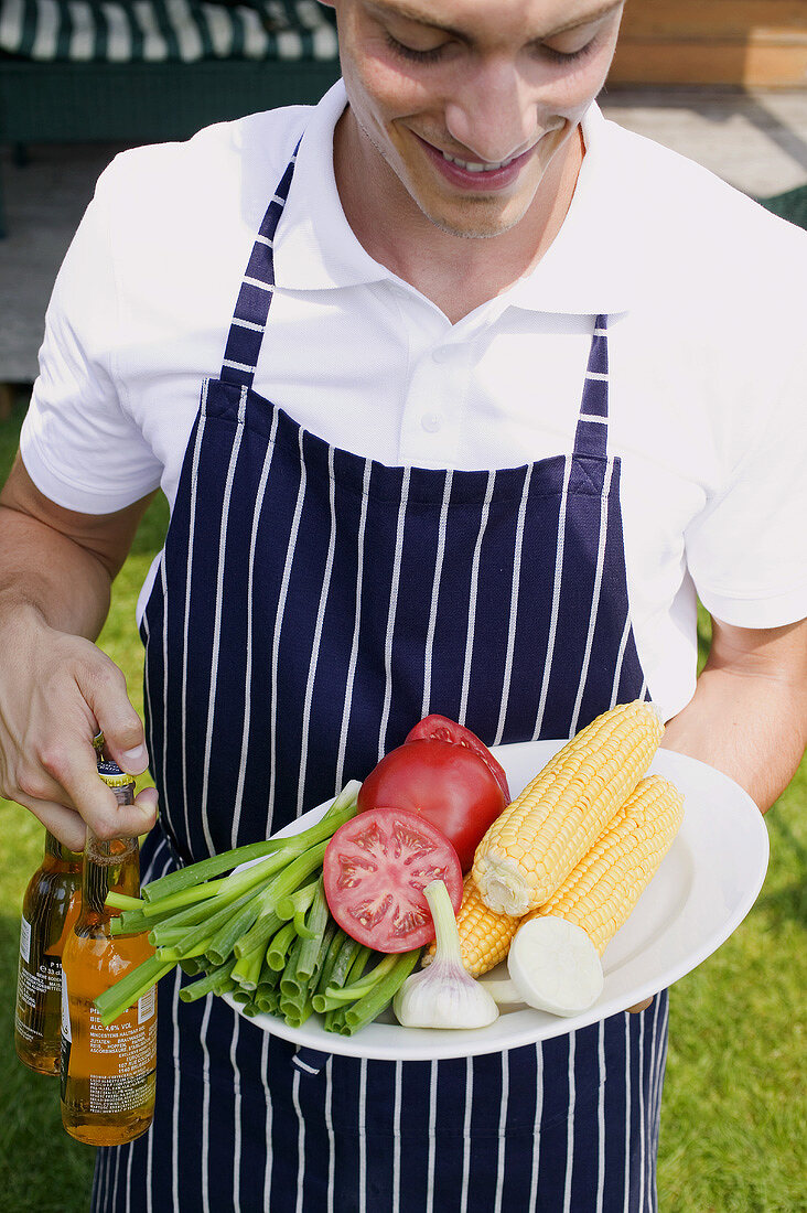 Young man in apron holding vegetables & beer at a barbecue