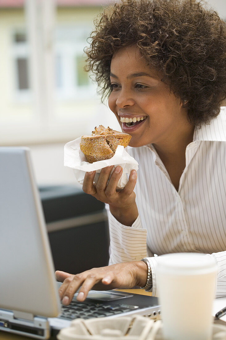 Woman eating muffin while working on computer