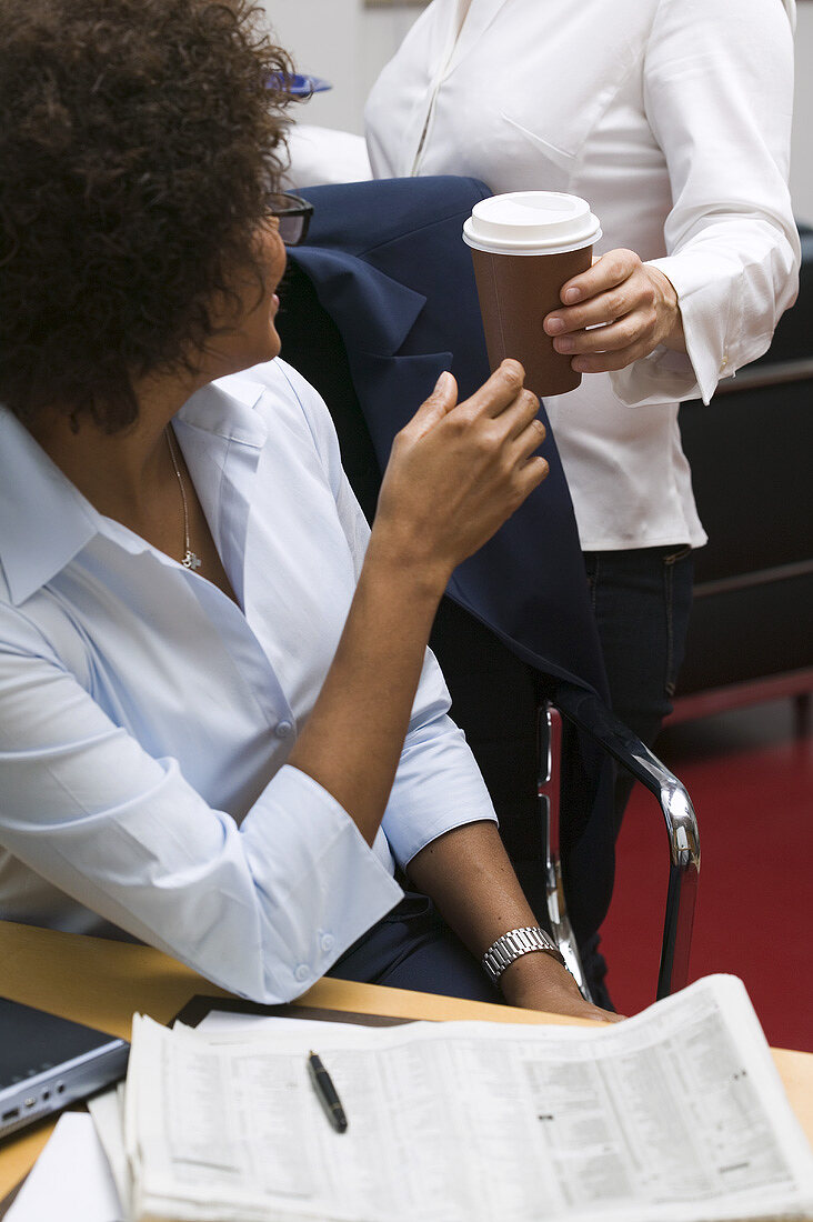Hand passing cup of coffee to woman in office